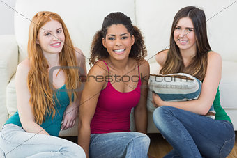 Portrait of young female friends on floor against sofa