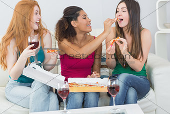 Happy female friends eating pizza with wine at home