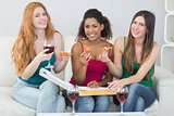 Happy young female friends with pizza and wine at home