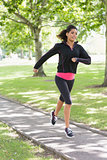 Healthy young woman jogging on pathway in park