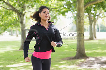 Beautiful healthy young woman jogging in the park