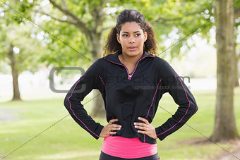 Tired healthy young woman standing in the park