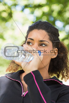 Close up of a tired woman drinking water in park