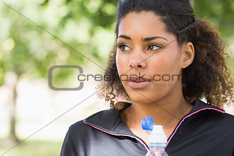 Close up of a tired healthy woman with water bottle in park