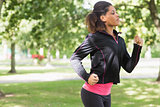 Side view of a beautiful healthy woman jogging in park