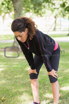 Tired woman taking a break while jogging in park