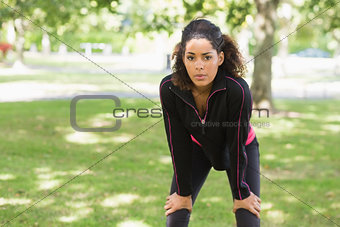 Tired young woman taking a break while jogging in park