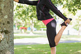 Side view of a woman stretching her leg during exercise at park