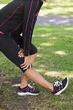 Mid section of woman stretching her leg during exercise at park
