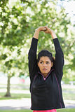 Woman stretching her hands during exercise at park