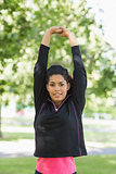 Healthy woman stretching her hands during exercise at park