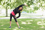 Full length of a healthy woman doing stretching exercise in park