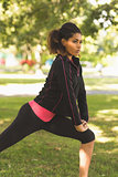 Serious healthy woman doing stretching exercise in park