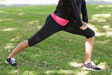Low section of woman doing stretching exercise in park