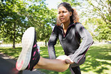 Sporty woman stretching her leg while standing in park