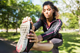 Pretty sporty woman stretching her leg in park