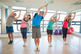 Fitness class and instructor standing in Namaste position