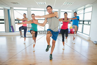 Full length of fitness class and instructor doing pilates exercise