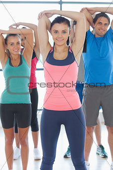 Portrait of sporty people stretching hands at yoga class