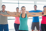 Portrait of sporty people stretching out hands at yoga class