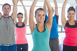 Portrait of sporty people stretching up hands at yoga class
