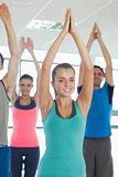 Fitness class with hands joined at exercise studio