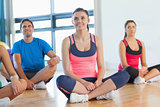 Smiling fitness class and instructor sitting on floor
