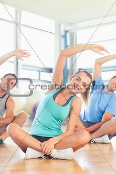 Fitness class and instructor sitting and stretching hands