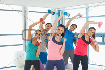 People lifting dumbbell weights with trainer in gym