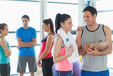 Fit couple with friends in background in exercise room