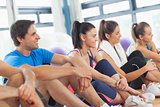 Side view of a group of fitness class sitting in row