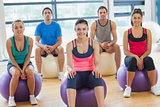 Smiling people sitting on exercise balls in the bright gym