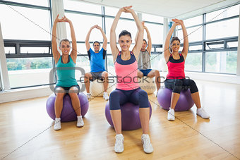 Smiling people sitting on exercise balls and stretching up hands