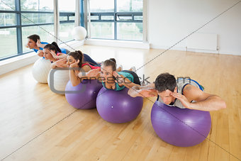 Fitness class exercising on fitness balls in a row