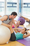 Trainer helping woman at fitness studio