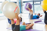 Class exercising with fitness balls at a bright gym