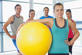 Instructor holding exercise ball with fitness class in background