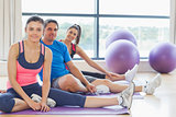 Fitness class and instructor sitting on exercise mats