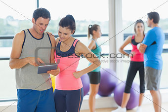 Fit couple looking at digital table with friends chatting in background