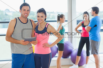 Fit couple holding digital table with friends chatting in background
