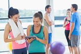Fit women looking at digital table with friends chatting in background