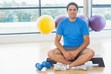 Young man sitting with dumbbells in fitness studio