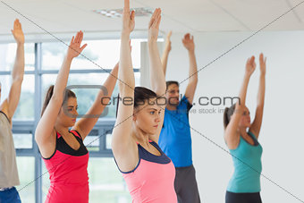 Side view of sporty people raising hands at yoga class