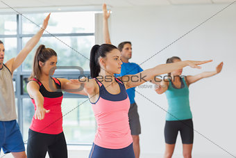 Sporty people stretching out hands at yoga class