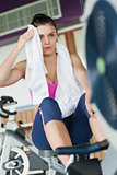 Tired young woman working out on row machine