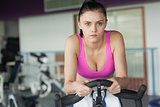 Determined woman working out at spinning class