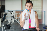 Woman drinking water while working out at spinning class