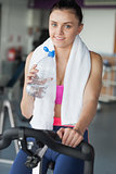 Tired woman drinking water while working out at spinning class