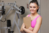 Smiling female trainer with clipboard in the gym