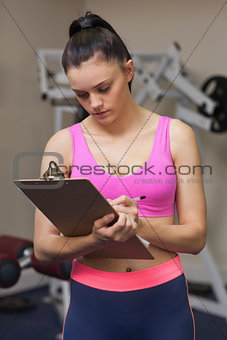 Serious female trainer with clipboard in gym